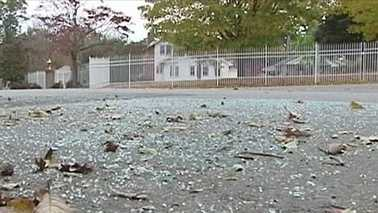 Broken glass remained at the scene of a hit and run involving a postal worker.