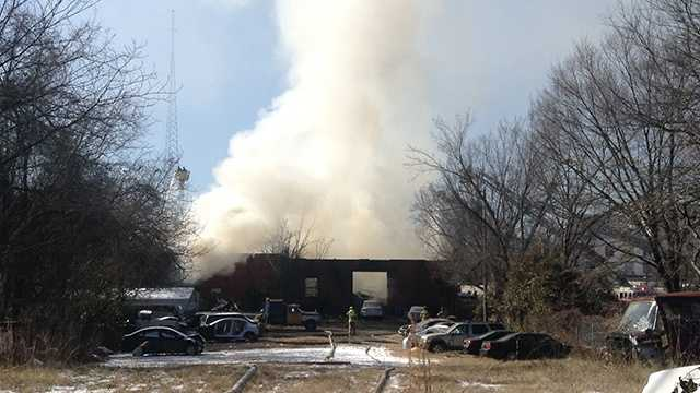Four firefighters were injured after a roof collapsed while battling a large fire near downtown Greensboro.