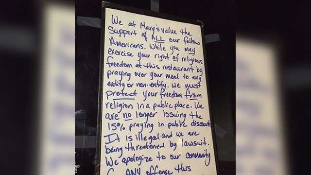 A sign outside Mary's Diner announces they are no longer offering a 15 percent prayer discount.