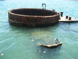 In the U.S.S. Arizona Memorial Museum (Oahu, Hawaii) you can see the ship underneath the waters like a ghost ship. Some parts still intact from the invasion on Pearl Harbor.