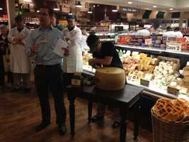 They don't cut a ribbon, they crack a wheel of Parmigiano-Reggiano cheese from Italy.