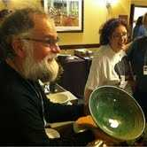 Brian McCarthy, co-founder of Odyssey Center for Ceramic Arts & Highwater Clays admires the potters work for this year's Empty Bowl luncheon.