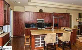The kitchen has cherry stained-cabinets, granite counter tops and a cooking island