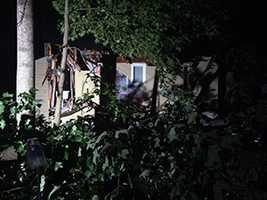 From the street, the inside of a bathroom is visible in one damaged home.