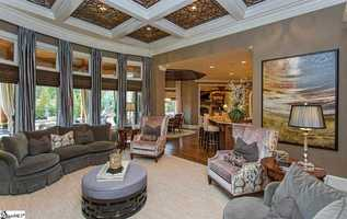 The Great room includes a fireplace, custom mantel, a one of a kind coffered ceiling and a wall of windows.