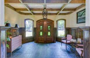 The home's entry features antique imported doors with Italian paneled glass.