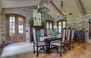 Two sets of French doors with beveled glass lead to the patio. It features hickory floors and a fire place with an antique hand-carved mantel.