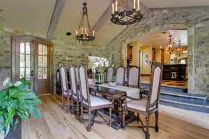 The dining room has a textured ceiling with exposed beams, wrought iron chandeliers and stone walls.