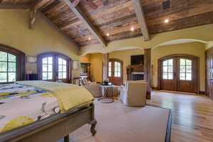 The master bedroom suite has a sitting area, fireplace, wide plank hickory floors, rough-hewn exposed beam ceiling, walk-in closet, and an 18'x14' spa-style bath.