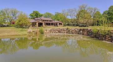 The home has more than 2,300 square feet of covered outdoor living areas, mature landscaping and a pond.