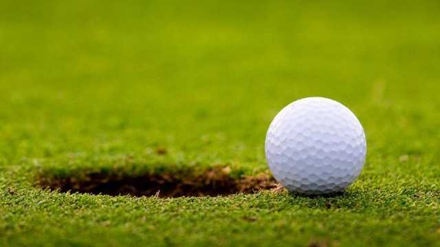 Golf ball on edge of hole