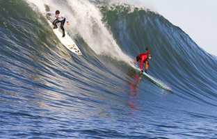 Peter Mel, wearing a red shirt on the right, glides down a wave face. Photo by Tony Canadas / Mavericks Invitational
