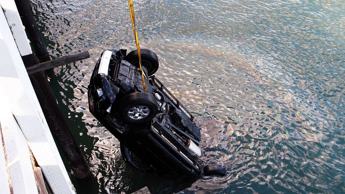 An SUV is lifted out of the ocean after a 16-year-old boy drove off the Santa Cruz Wharf. (Jan. 28, 2013 / Photo by Tim Cattera)