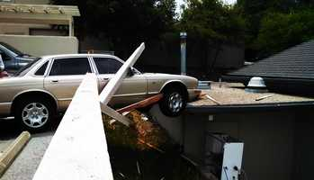A car busted through a fence and partially landed on a roof after the driver tried to back out of a parking space in Monterey.  (May 31, 2014)