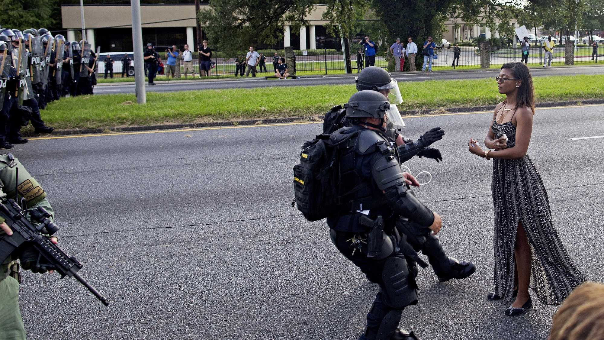 This is another view of the viral image of a protester being confronted by police officers in riot gear in front of the the Baton Rouge Police Department Headquarters in Baton Rouge, La., July 9, 2016.  AP Photo/Max Becherer