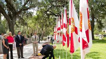 """Florida Attorney General Pam Bondi and Gov. Rick Scott (kneeling) gathered Friday in Tallahassee in front of a memorial for the victims of the Orlando massacre. """"The memory of this horrific tragedy will never be forgotten, as well as the legacies of each of the 49 victims,"""" Scott said. """"While we can never completely heal from the pain of such loss, we continue to be reminded of each life taken in Orlando and their individual impact on so many.""""Photo courtesy of the Office of Gov. Rick Scott."""