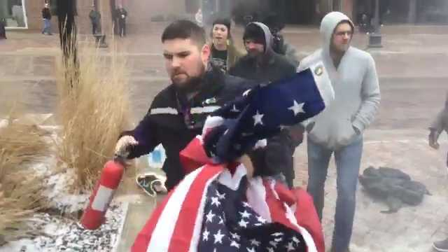Man rescues burning USA  flag from Iowa City protesters
