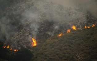 Wildfire slowly creeps down Mount Manuel into the Big Sur Valley.