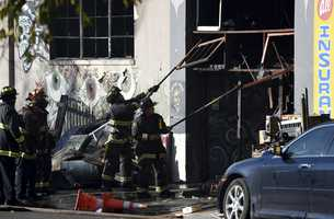 Firefighters clear an entry to a smoldering building after a fire tore through a warehouse party early Saturday.