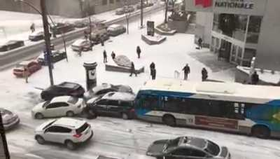 Montreal buses, cars, police cruiser, snow plow slide down Beaver Hall Hill