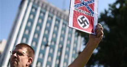 Kirt Moody of Columbia holds a sign during a rally to take down the Confederate flag at the South Carolina Statehouse (AP Photo/Rainier Ehrhardt)