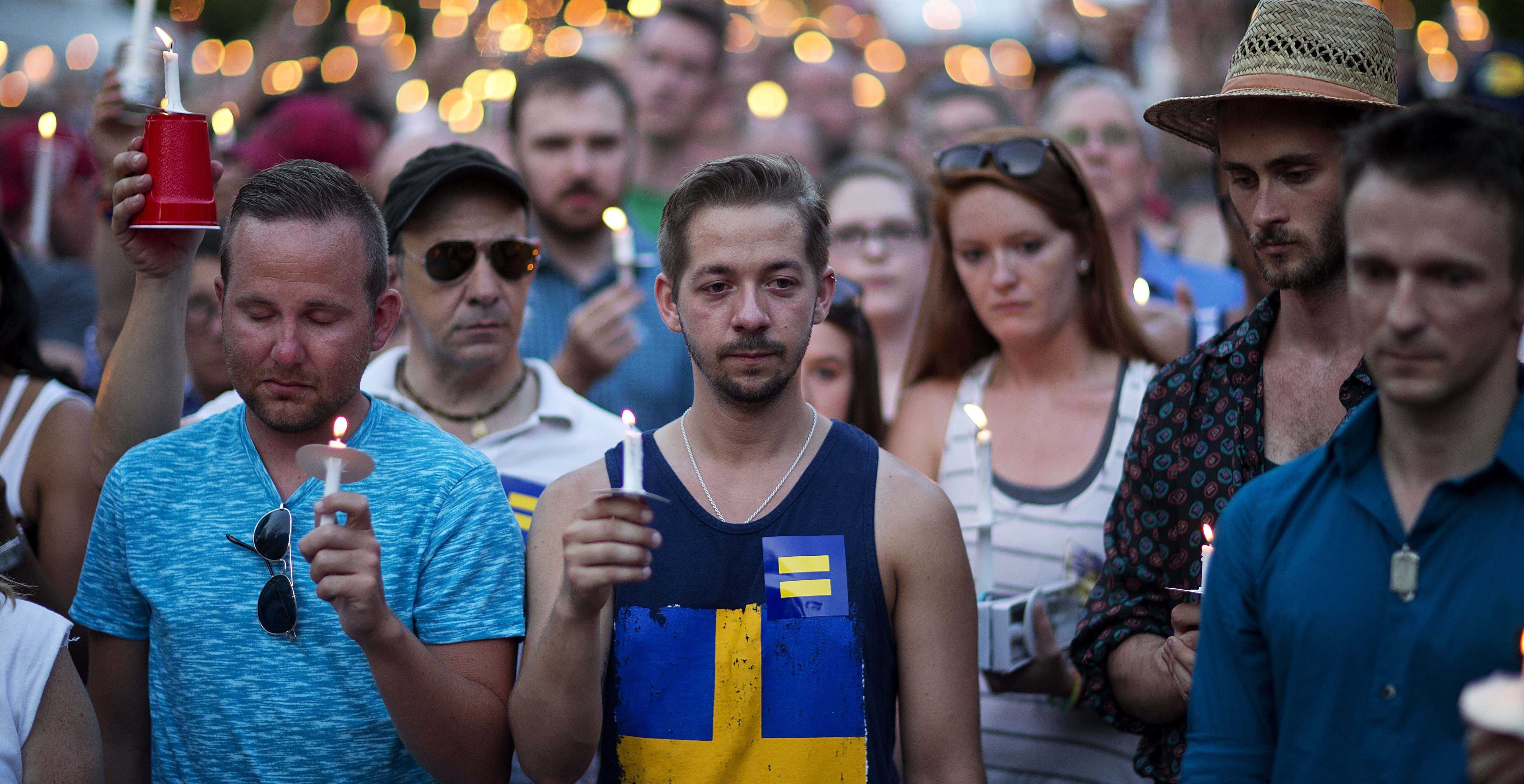 Mourners observe a moment of silence during a vigil for victims of a fatal shooting at an Orlando nightclub, Sunday, June 12, 2016, in Atlanta. (AP Photo/David Goldman)