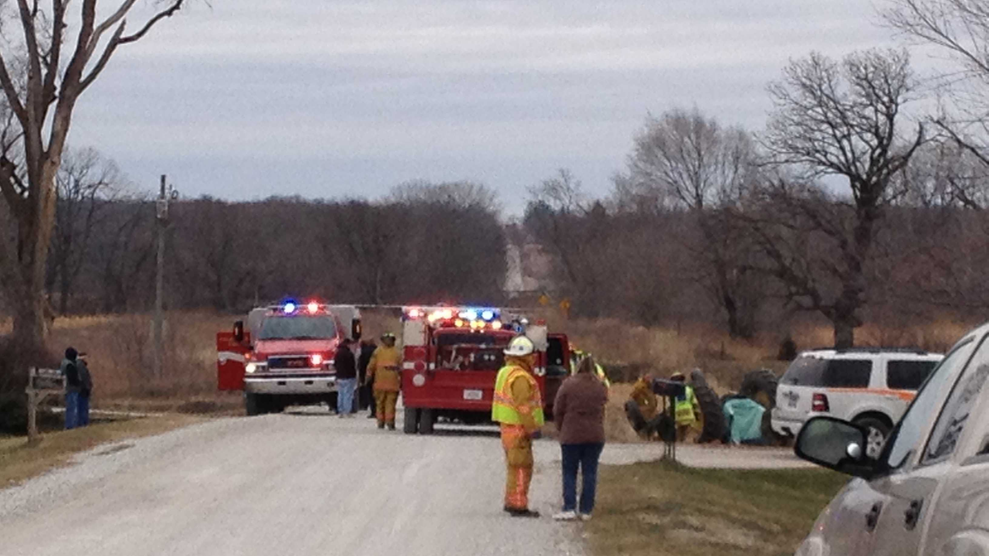 Rescue crews work to free a 9-year-old girl who is pinned under a tractor near Cambridge.