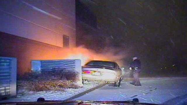 Officer approaches the car with flashlight.