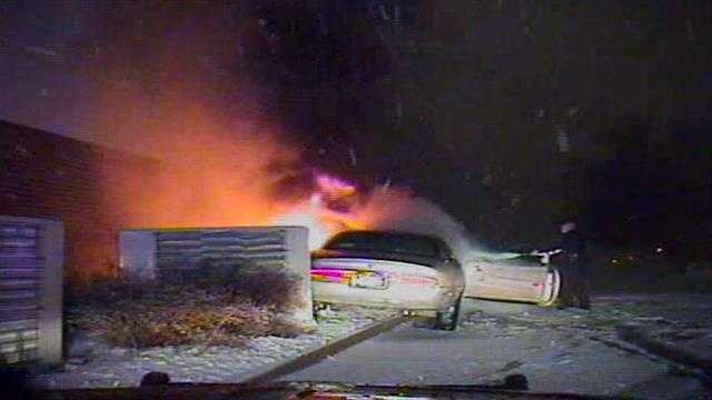 Helpers pull man away from the car as the officer tries to put out the fire.