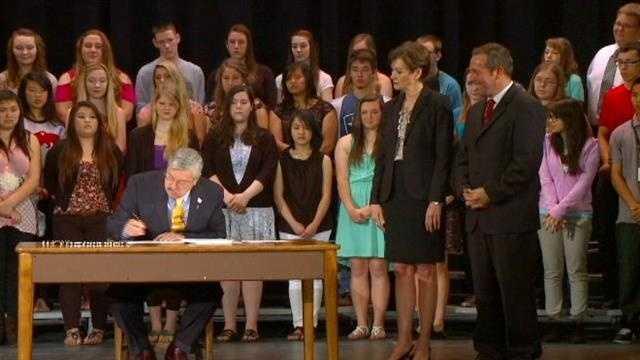 Iowa Gov. Terry Branstad signs a bill to reform Iowa's education system.