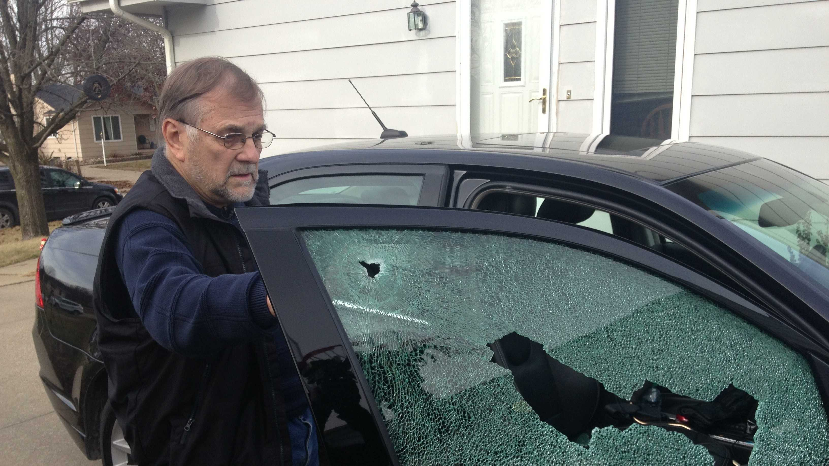 Larry Chiles shows KCCI his car with window shot out.