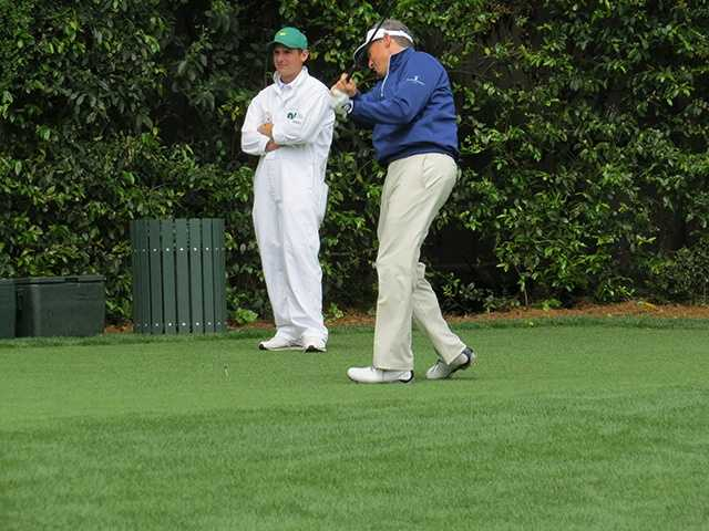 Nate McCoy watches as his dad Mike McCoy tees off on the 5th hole at Augusta National Golf Club.