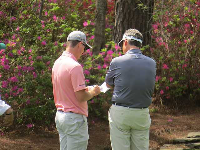 Mike McCoy checks out the playing notes of 2013 U.S. Open champion Justin Rose.