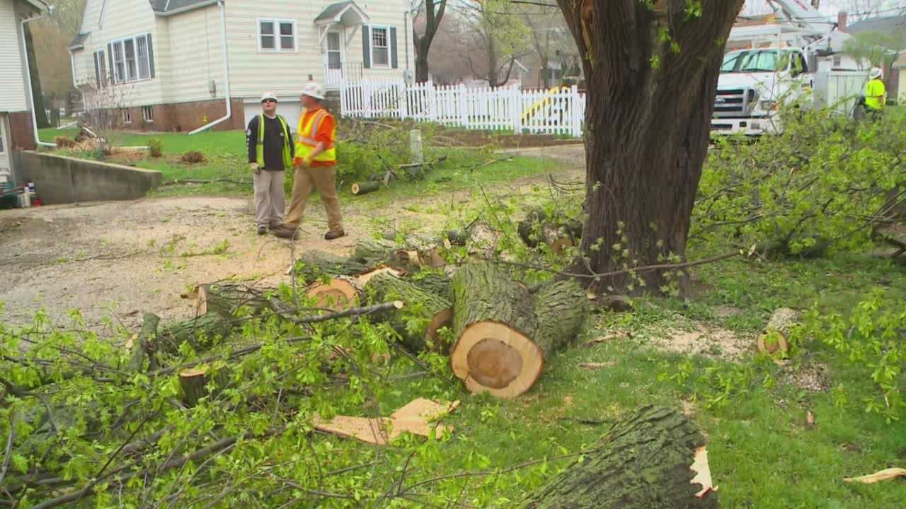Crews work to restore power and cut down damaged trees after storms hit Iowa Sunday.