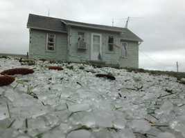 Hail hits home in Casey, Iowa -- windows broken out, hail covering ground around the home