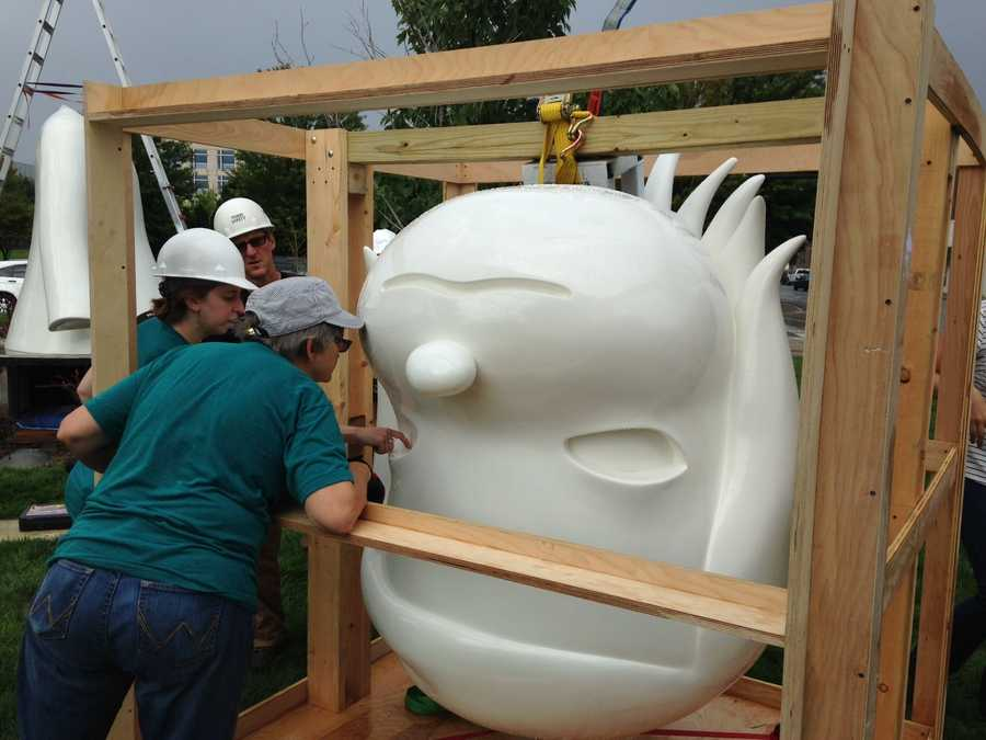The head is unwrapped and readied to be lifted into place by a crane.