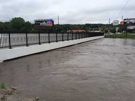Flood water up to bottom of bridge on Grand Avenue at 63rd, 10:30am Thursday