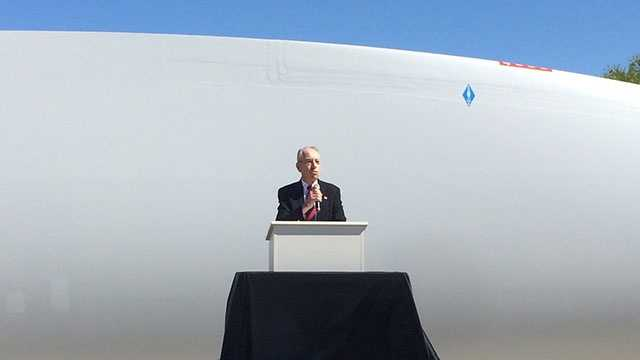 Sen. Charles Grassley in front of a giant wind blade built for a wind turbine farm.