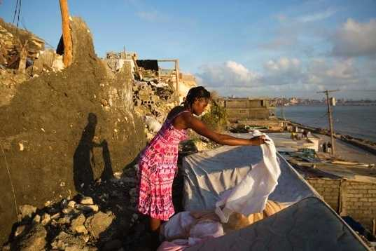 Andrenne Joseph dries her clothes near her destroyed house caused by Hurricane Matthew, in Jeremie, Haiti. Saturday Oct. 8, 2016. Aid has begun pouring into the hard-hit town, where thousands of homes were damaged or destroyed and many people were running low on food and facing an increased risk for cholera.