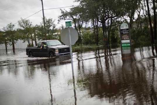 A pickup truck wades through a flooded street after Hurricane Matthew passed through St. Simons Island, Ga., Saturday, Oct. 8, 2016. A weakening Hurricane Matthew continued its march along the Atlantic coast Saturday, lashing two of the South's most historic cities and some of its most popular resort islands, flattening trees, swamping streets and knocking out power to hundreds of thousands.