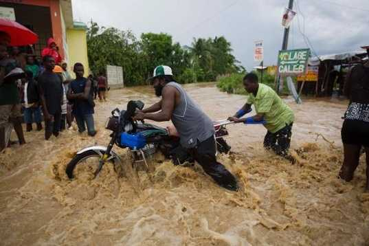 Men push a motorbike through a street flooded by a river that overflowed from heavy rains caused by Hurricane Matthew in Leogane, Haiti, Wednesday, Oct. 5, 2016. Rescue workers in Haiti struggled to reach cutoff towns and learn the full extent of the death and destruction caused by Hurricane Matthew as the storm began battering the Bahamas on Wednesday and triggered large-scale evacuations along the U.S. East Coast. (AP Photo/Dieu Nalio Chery)