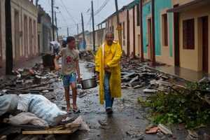 Residents carry food down a street strewn with rubble caused by Hurricane Matthew in Baracoa, Cuba, Wednesday, Oct. 5, 2016. The hurricane rolled across the sparsely populated tip of Cuba overnight, destroying dozens of homes in Cuba's easternmost city, Baracoa, leaving hundreds of others damaged. (AP Photo/Ramon Espinosa)