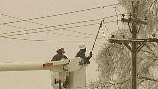Power Crews in bucket ice storm trees limbs - 22311892