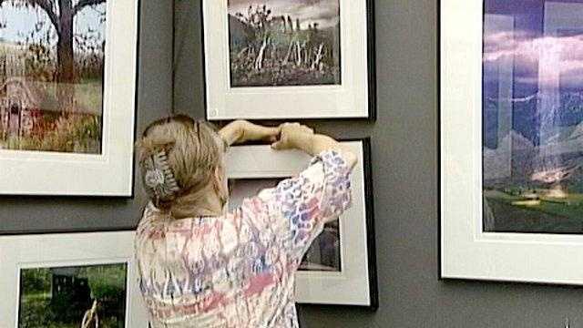 Des Moines Arts Festival artist hangs picture - 19873679