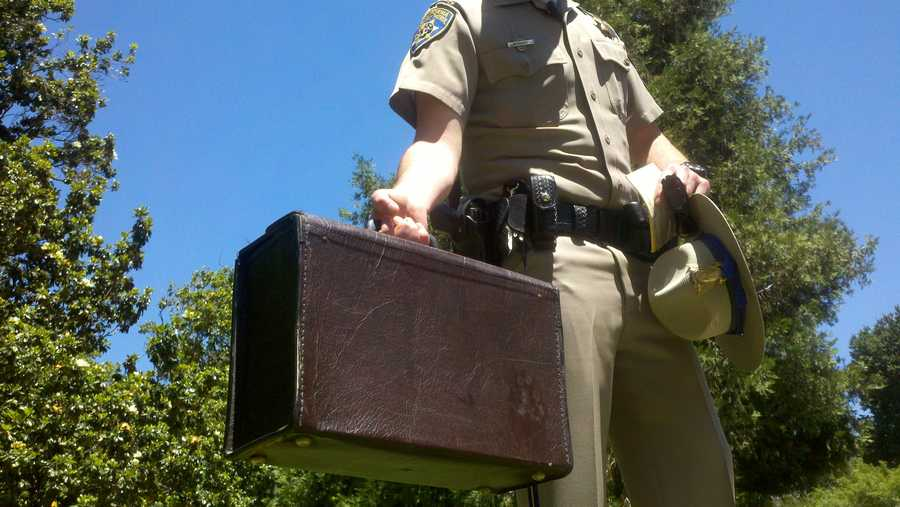 CHP officer Sean Kennedy shows a briefcase that caused a bomb scare in Capitol Park.