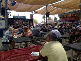 Fair-goers eat lunch while listening to the band Vintage Fare.