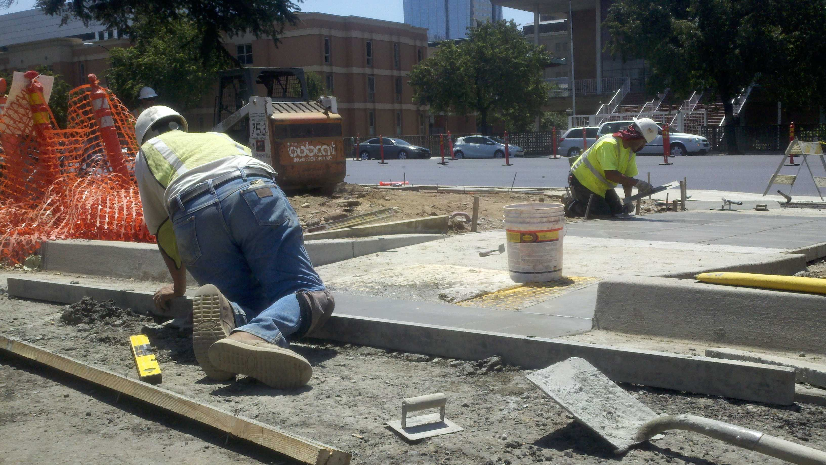 Cement masons work on a new sidewalk outside Sacramento's train station.