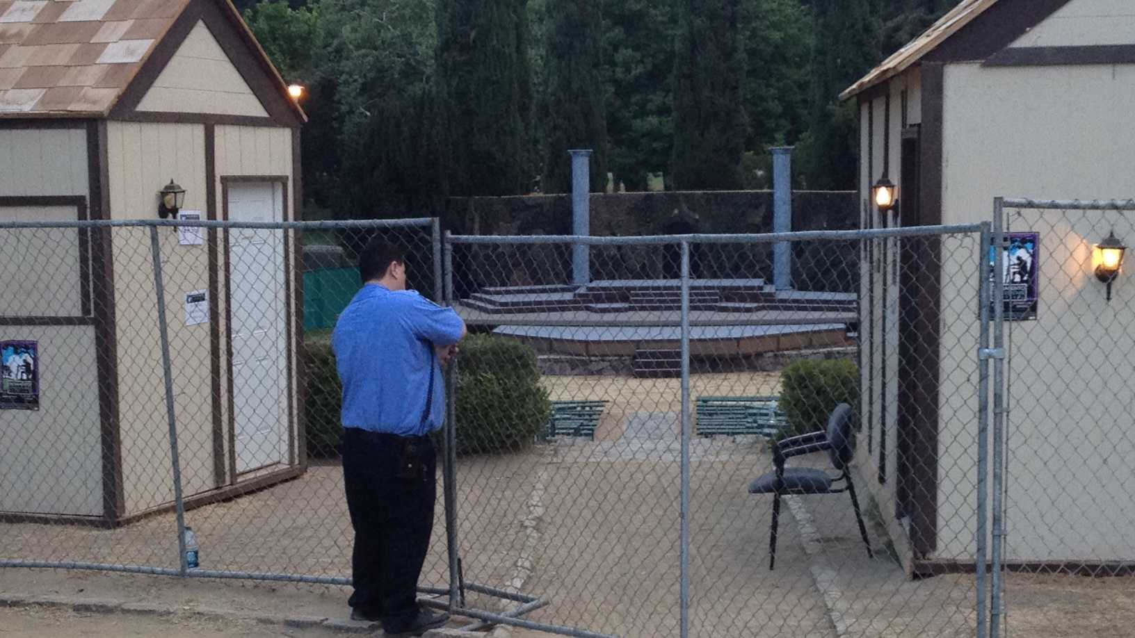 A guard secures a gate outside the Sacramento Shakespeare Festival.