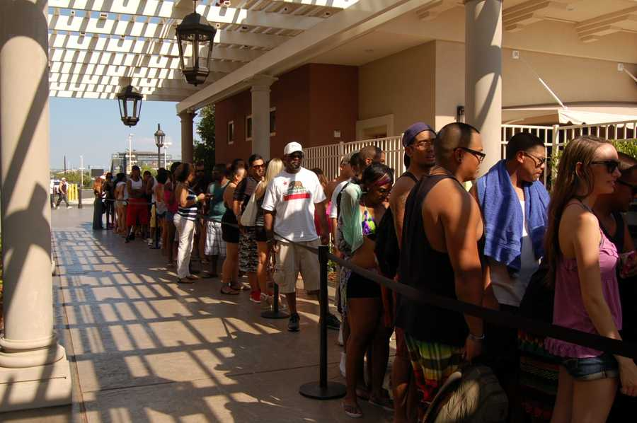 A line of folks waiting to get into the pool party.