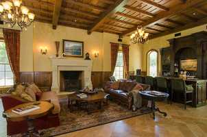 The grand room is the heart of the home, with an impressive stone fireplace and travertine flooring.